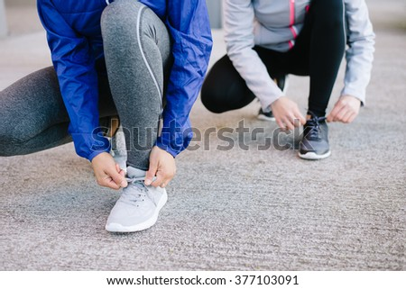 Women lacing sport shoes and getting ready for urban running. - stock photo