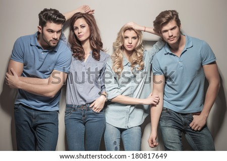 women leaning against their handsome men . two couples of young casual people standing together in studio - stock photo