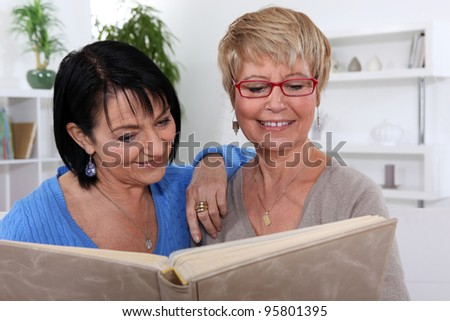 Women looking at a photo album - stock photo