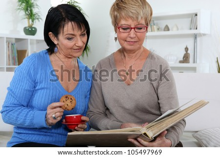 Women looking at an album - stock photo