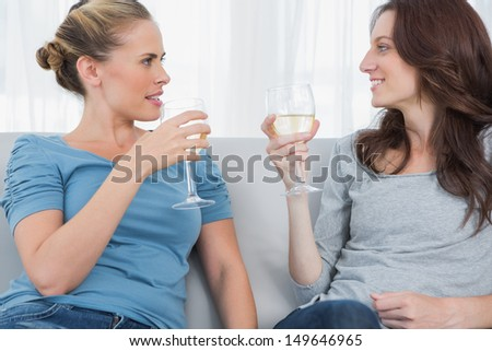 Women looking at each other clinking their wine glasses while sitting on the sofa - stock photo