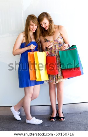 Women looking at shopping bags - stock photo