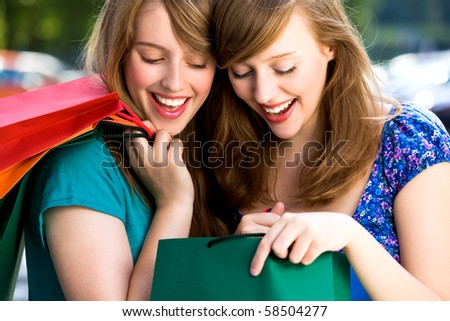 Women looking in shopping bags - stock photo