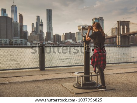 Women looking to New York through a telescope