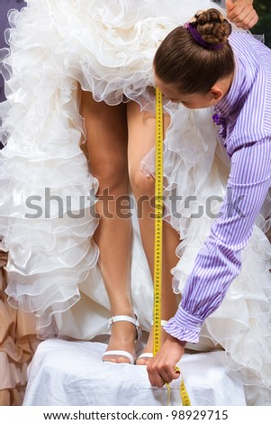 Women making adjustment to wedding gown in professional fashion designer studio - stock photo