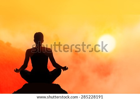 women meditating on high mountain in sunset background - stock photo