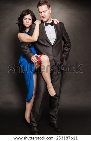 Women men relationship. Woman in blue dress and man with gun in suit on black background.