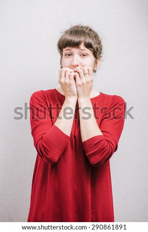 Women nervous nail biting. On a gray background. - stock photo