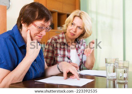 Women notary helping mature client drawing up of will - stock photo