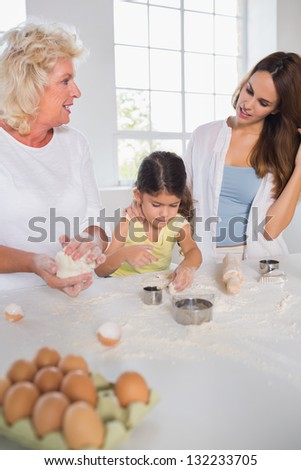 Women of a family baking together in the kitchen - stock photo