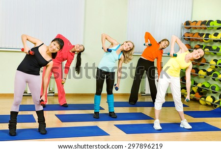 Women of Different Age (from 18 to 50) Doing Aerobics with Dumbbells - stock photo