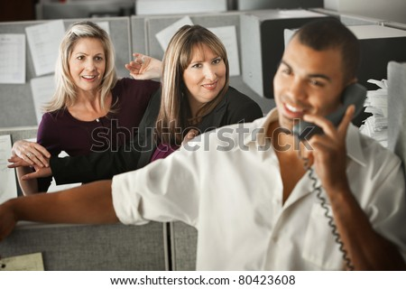 Women office workers flirt with handsome male coworker in office - stock photo