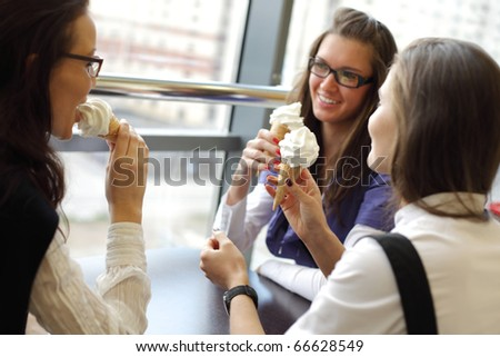 women on foreground licking ice cream - stock photo