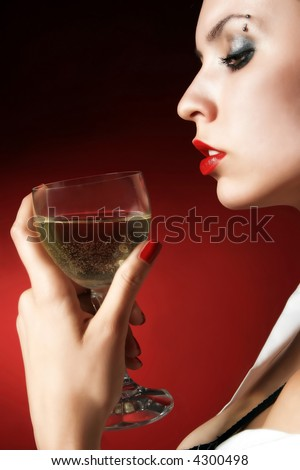 women on red is holding a glass of white wine - stock photo