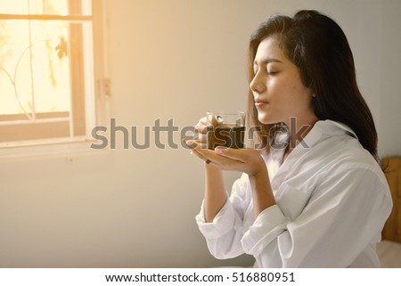 Women on the bed with coffee cup in bedroom on holiday,selective and soft focus ,vintage tone
