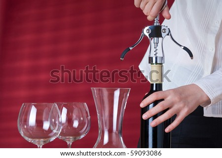 Women opening red wine by corkscrew. Next to her stay two wineglasses and carafe. Red background behind her with sun beams and shades. - stock photo