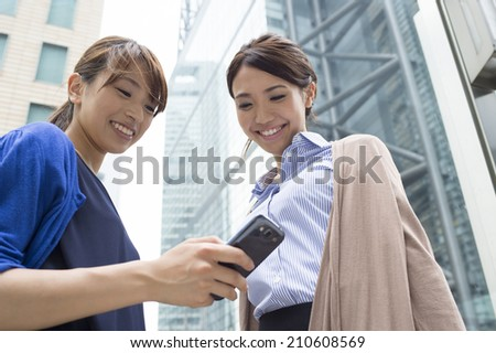 Women operating the smart phone while conversation with a smile - stock photo