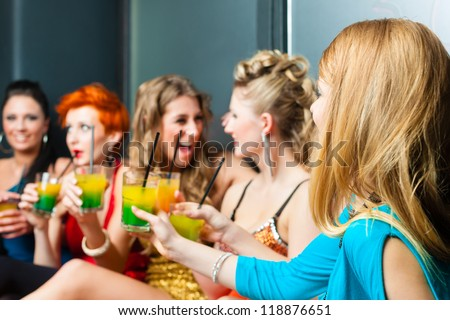 Women or models in club or disco drinking cocktails having fun - stock photo
