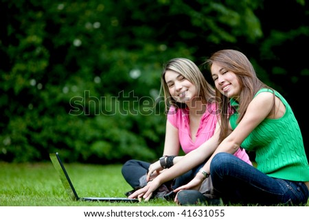 women outdoors with a laptop computer and smiling - stock photo