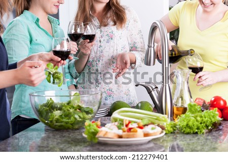 Women party with wine and healthy food in kitchen - stock photo