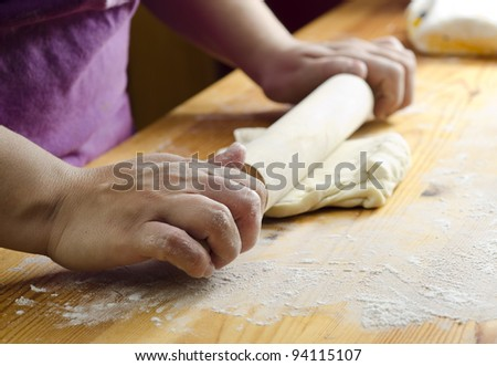 Women pastry using a rolling pin to make bread in her work
