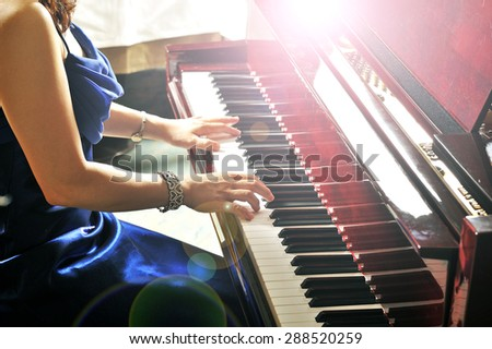 Women playing the grand piano in the room - stock photo