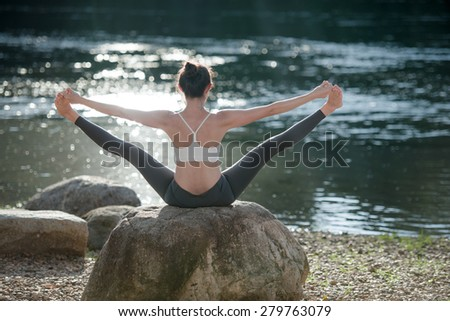 Women playing yoga at the river,peaceful place,natural location, straddle