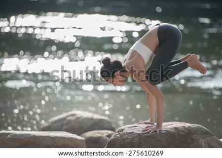 women playing yoga near the river, - stock photo