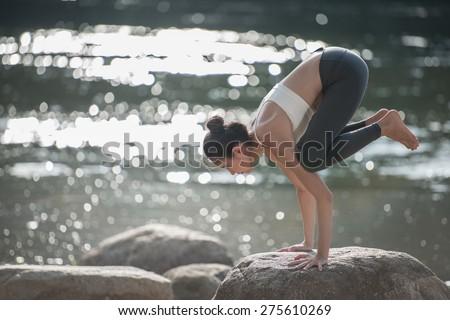 women playing yoga near the river, - stock photo