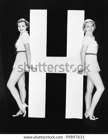 Women posing with huge letter H - stock photo