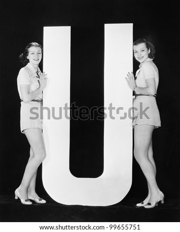 Women posing with huge letter U - stock photo
