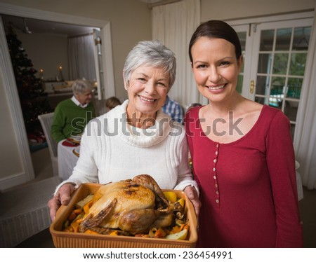 Women posing with roast turkey in front of their family at home in the living room - stock photo