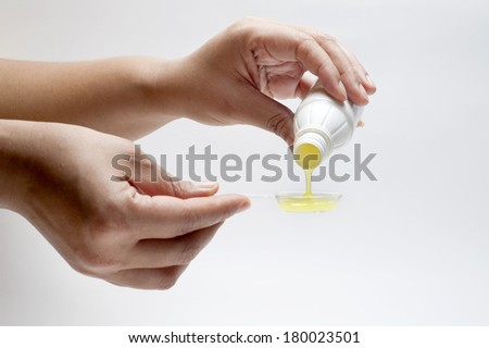 Women pouring medicine into spoon.