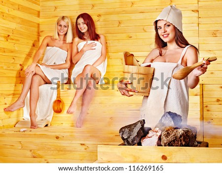 Women pouring water on rock in sauna. - stock photo