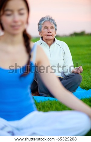 Women practicing yoga exercises outdoors ? fitness concepts - stock photo