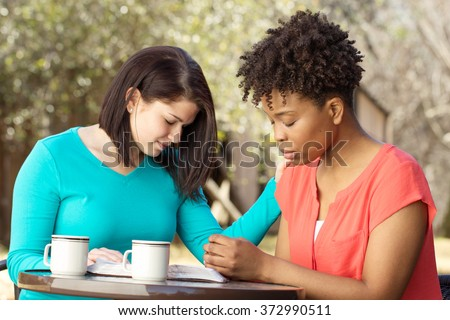 Women praying for each other. - stock photo