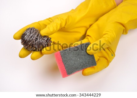 women protecting hands with rubber gloves from detergents and holding silver kitchen scraper and sponge for dishes cleaning on white background - stock photo