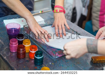Women putting silk on water surface for color inks printing into silk, ebru art - stock photo