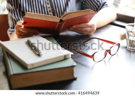 women read a book on wood table in warm house - stock photo