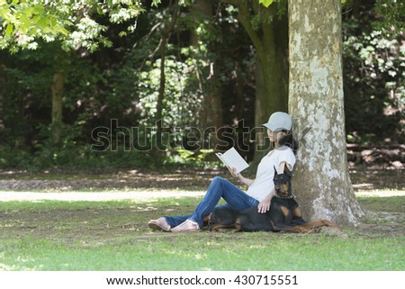Women read a book with the doberman
