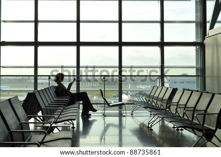 Women reading and waiting in the airport departure lounge - stock photo