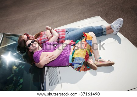 Women resting on the hood of an old car - stock photo