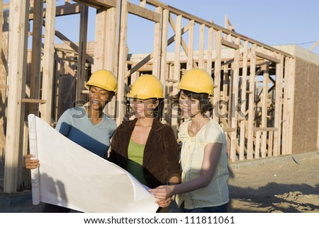 Women reviewing blueprint at construction site