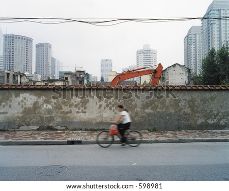 Women riding pass building works in shanghai in motion blur