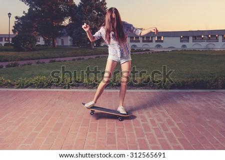 Women riding skateboard toned image - stock photo