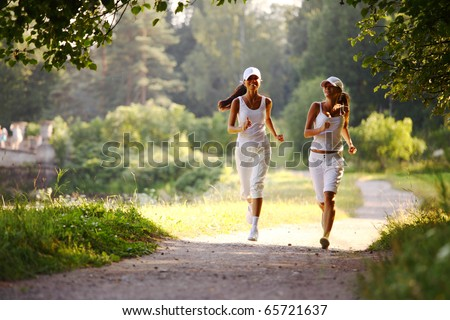 women run by sunny park - stock photo
