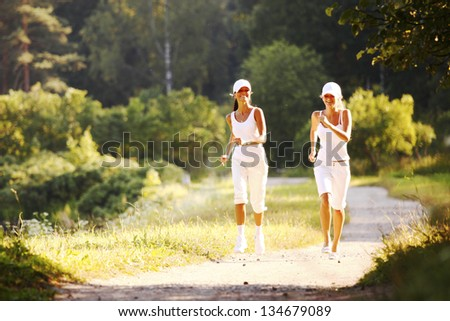 women run by sunny park alley - stock photo