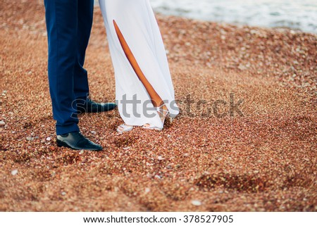 Women's and men's feet in the sand