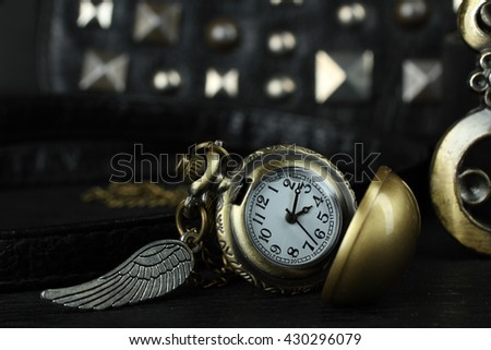 women's bag with old clocks as a pendant on a black background - stock photo