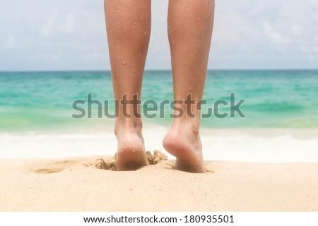 Women's beautiful legs on the beach - stock photo